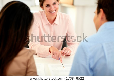 Portrait of young caucasian bank manager working on agreement contract and explaining the application form to a businessman at indoors - stock photo