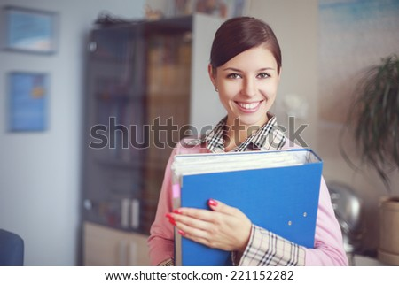 Portrait of young caucasian business woman in pink vest with ring binder at her office - stock photo