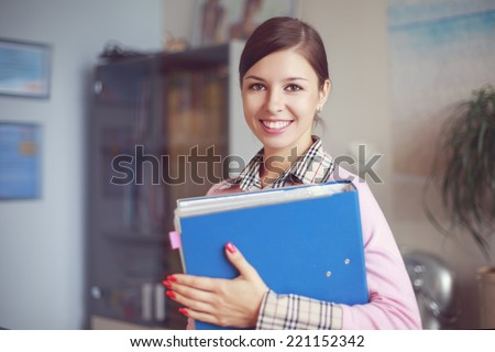 Portrait of young caucasian business woman in pink vest with ring binder at her office