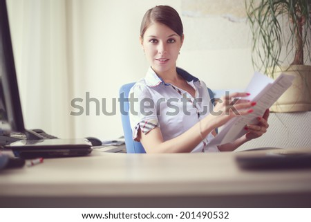 Portrait of young caucasian business woman in white shirt with short sleeves  at her office
