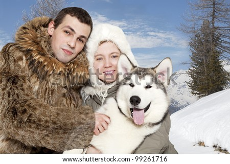 Portrait of young caucasian couple with a malamute puppy - stock photo