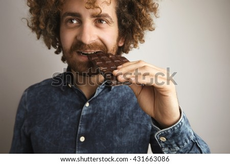 Portrait of young caucasian curly hair happy man with healthy skin bites organic freshly baked chocolate bar with side of mouth, looking in side of camera, close focus on hand
