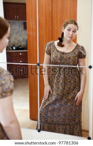 Portrait of young Caucasian female in dress standing against mirror and looking at herself in domestic room - stock photo