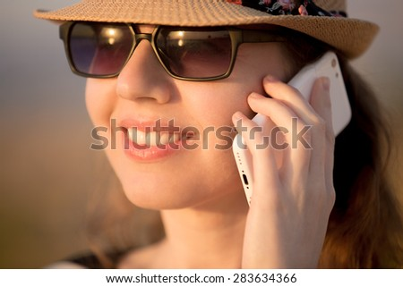 Portrait of young Caucasian happy smiling woman in cute straw hat and sunglasses using cellphone, making call in sunlight, close up