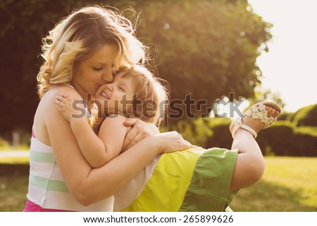 Portrait of young caucasian pregnant woman embracing with her daughter in the meadow of the park. - stock photo