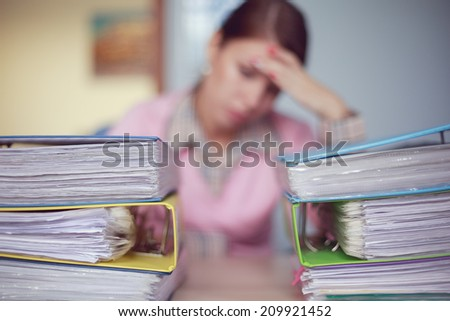 Portrait of young caucasian sad business woman with stacks of ring binders sitting at the desk - stock photo