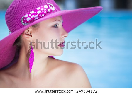 Portrait of young caucasian thoughtful lady posing in pink hat - stock photo