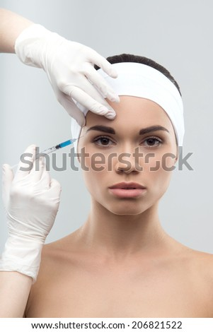 Portrait of young Caucasian woman getting cosmetic injection, isolated over grey background - stock photo