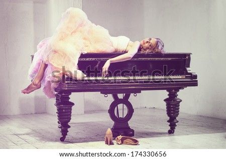 Portrait of young caucasian woman in fluffy dress lying on the cover grand grand piano - stock photo