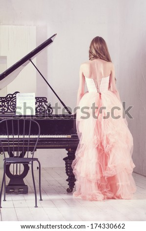 Portrait of young caucasian woman in fluffy dress standing near the grand piano - stock photo