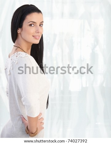 Portrait of young caucasian woman, looking at camera, smiling. Copy space on right.? - stock photo