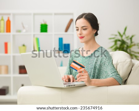 portrait of young caucasian woman looking at laptop, holding credit card and spending money online while relaxing at home - stock photo