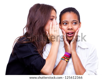 portrait of young caucasian woman telling a secret to an african american woman over a white background - stock photo