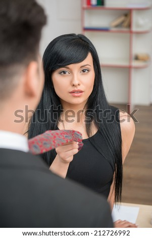 Portrait of young charming businesswoman flirting and pulling her colleague by the tie in office, looking at the camera - stock photo
