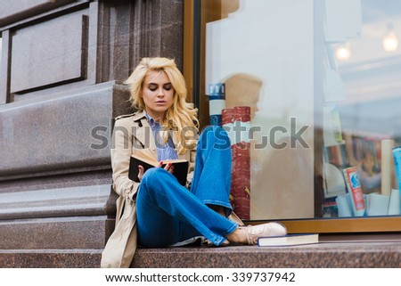 Portrait of young charming female student with luxury blonde hair reading book before start lectures in University, beautiful woman with trendy look posing while sitting with text book on a shop sill - stock photo