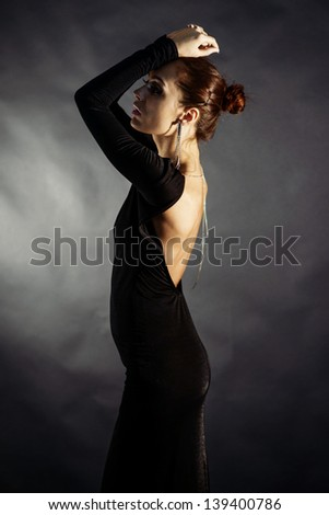 Portrait of young charming girl in black dress - stock photo