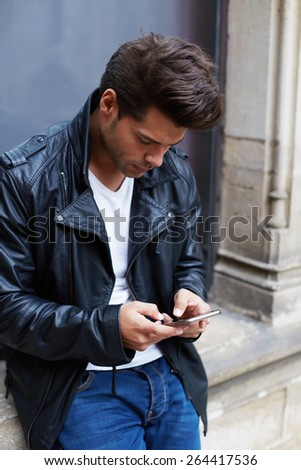 Portrait of young charming man using busy smart phone while chatting with someone, attractive stylish male student typing message on his cell phone while standing outdoors in the city - stock photo