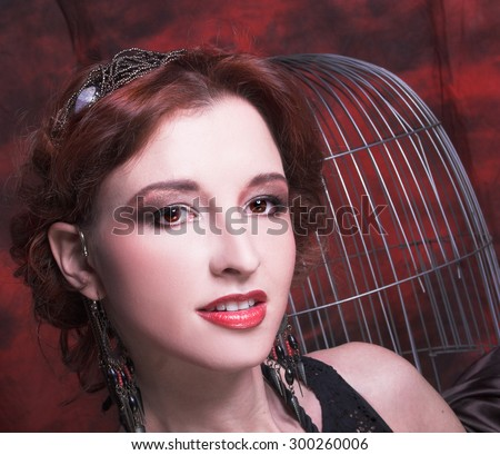 Portrait of young charming woman in ethnic image posing near cage.