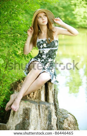 Portrait of young charming woman propping up her face, sits at summer green park. - stock photo