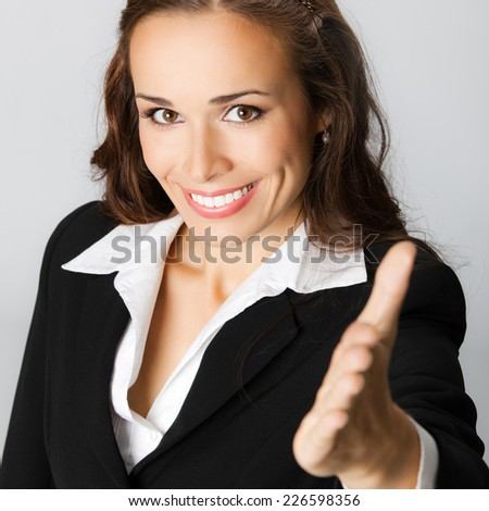Portrait of young cheerful beautiful business woman giving hand for handshake, against grey background - stock photo
