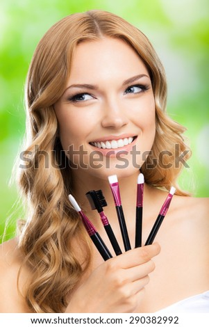 Portrait of young cheerful blond woman with make up tools, outdoors. Beauty, visage and cosmetics concept. - stock photo