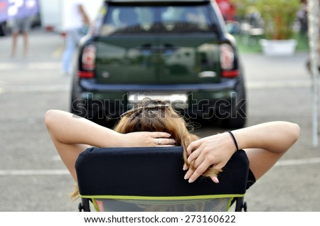 Portrait of young cheerful blonde woman holding hand behind head, relaxing at the parking in front of his car before a long journey. - stock photo