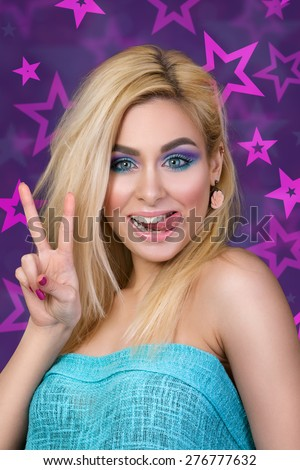 Portrait of young cheerful blonde woman showing her tongue and victory sign - stock photo