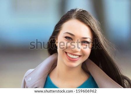 Portrait of young cheerful brunette posing outdoors - stock photo