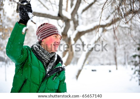 Portrait of young cheerful man outdoor in winter park holding tree branch