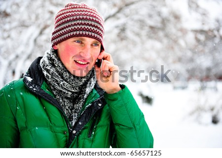 Portrait of young cheerful man outdoor in winter park speaking mobile phone