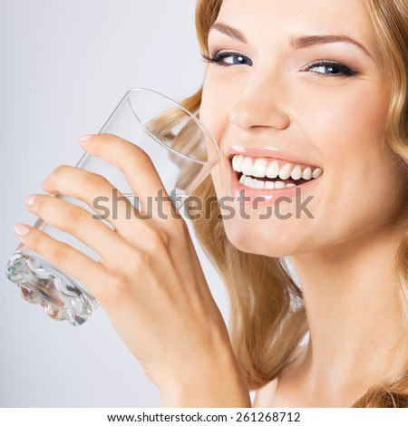 Portrait of young cheerful smiling woman drinking water, against grey background. Healthy lifestyle and dieting concept. - stock photo