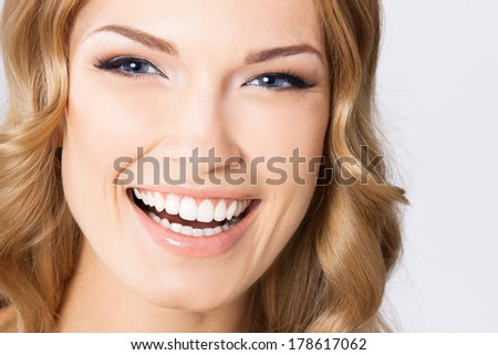 Portrait of young cheerful smiling woman, over gray background - stock photo