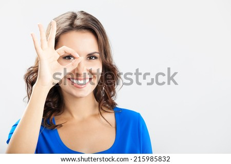 Portrait of young cheerful smiling woman showing okay gesture, with copyspace, over grey  - stock photo