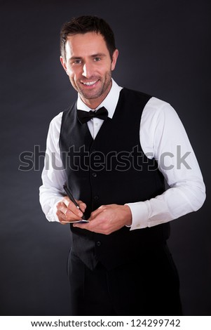 Portrait of young cheerful waiter on black background - stock photo