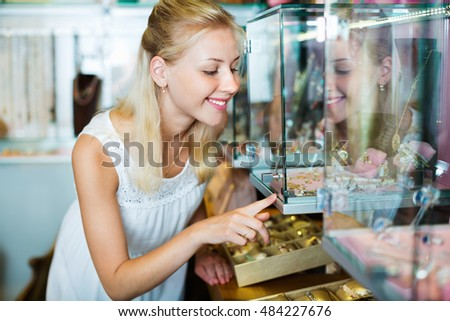 Portrait of young cheerful woman standing next to glass showcases in shop with bijouterie