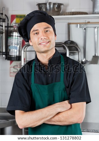 Portrait of young chef with hands folded standing in commercial kitchen