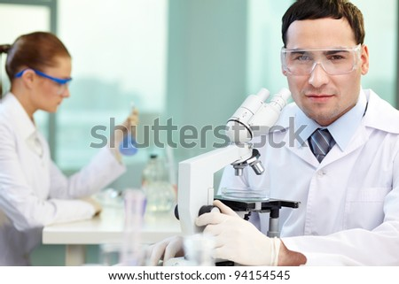 Portrait of young clinician looking at camera in working environment - stock photo