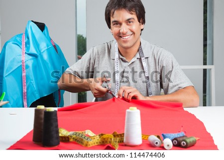 Portrait of young clothing dressmaker cutting red fabric with polyester threads on cloth - stock photo