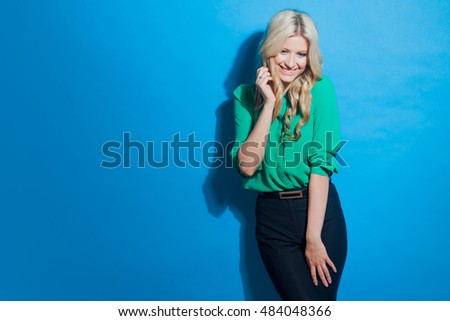 Portrait of young confident blonde, casual style, blue background
