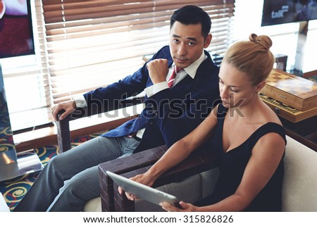 Portrait of young confident business men and secretary preparing for the conference while sitting in modern office space,successful female and male entrepreneurs using touch pad while working together - stock photo