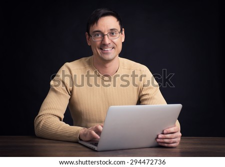 Portrait of young confident casual man with laptop
