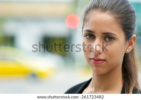 Portrait of young confident hispanic business person looking at camera and smiling in the street with cars passing behind - stock photo