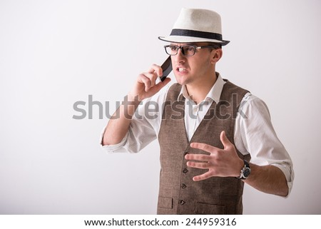 Portrait of  young confident man is wearing a hat is talking by phone on grey background. - stock photo