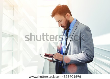 Portrait of young confident men employee dressed in elegant clothes working on digital tablet while standing in modern office space, successful male entrepreneur in suit using touch pad during break  - stock photo