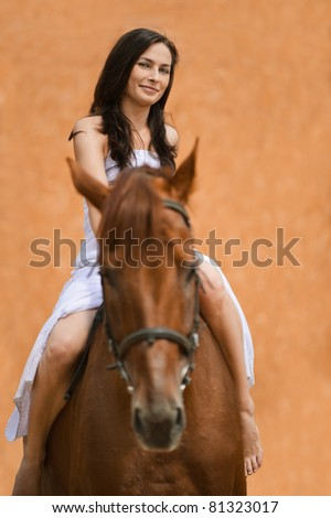 Portrait of young content long-haired brunette woman wearing white dress riding brown horse. - stock photo