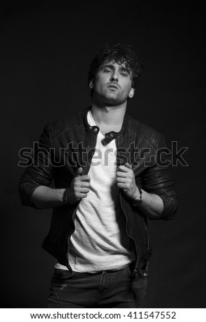 Portrait of young content man resting chin on fist, low key, black and white - stock photo