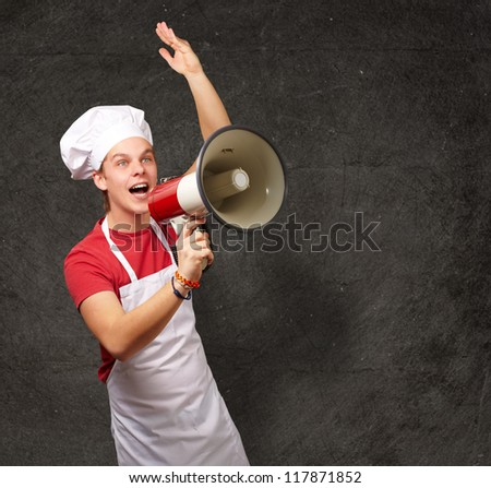 portrait of young cook man shouting with megaphone against a grunge wall - stock photo
