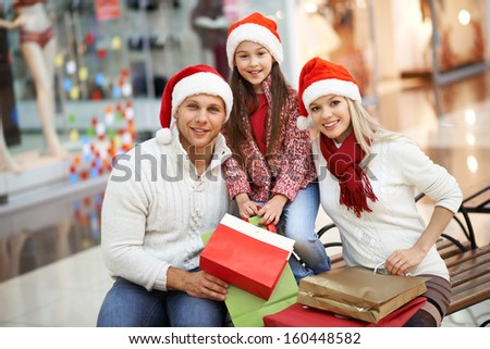 Portrait of young couple and their daughter in Santa caps looking at camera in the mall