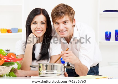 portrait of young couple cooking soup in their kitchen happy smile, looking at camera - stock photo