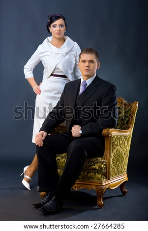Portrait of young couple dressed in elegant clothes. Man wearing three-pieces dark suit, sitting in armchair. Woman wearing white cocktail shirt with jacket, standing beside him. - stock photo